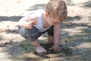 Dítě si hraje v louži - čistá pohoda přináší zdraví stejně jako vodní vysavač hyla